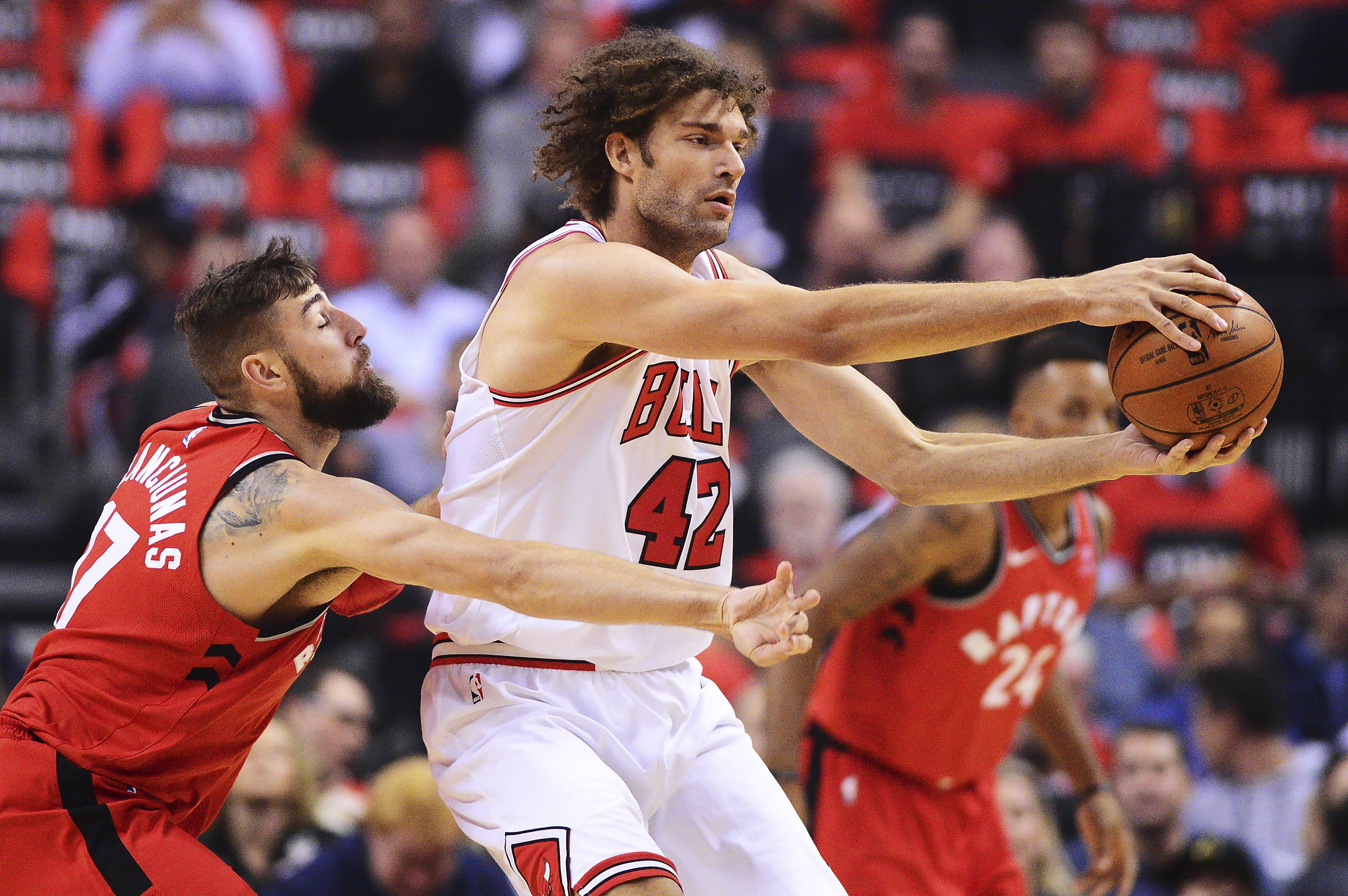 Chicago Bulls center Robin Lopez protects the ball from Toronto Raptors center Jonas Valanciunas during the first half of the game Thursday in Toronto.