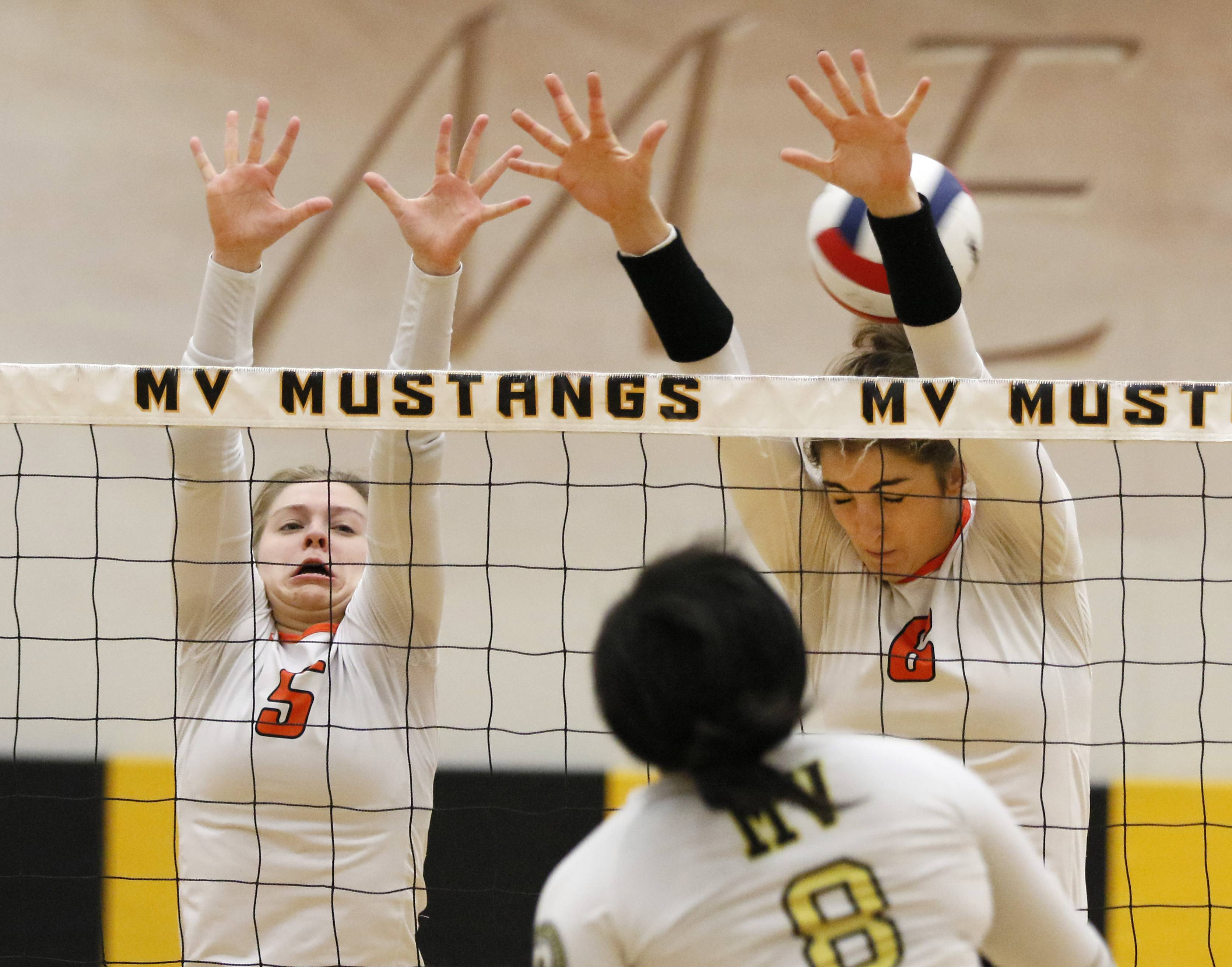 Metea Valley's Sydnee Marks (8) spikes the ball past St. Charles East's Ally Will (5) and Klaudia Sowizral (6) during girls volleyball action in Aurora Thursday.