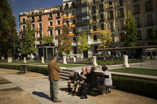 A group of elderly people talk about the political situation in Catalonia, near a building with Spanish flags fixed on balconies at the Oriente square in Madrid, Thursday, Oct. 19, 2017. Spain's government on Thursday immediately rejected a threat by Catalonia's leader to declare independence unless talks are held, calling a special Cabinet session for the weekend to activate measures to take control of the region's semi-autonomous powers. (AP Photo/Francisco Seco)