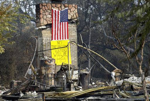A sign on the chimney of a home warns looters Wednesday, Oct. 18, 2017, after it was destroyed by wildfires in Glen Ellen, Calif. California fire officials have reported significant progress on containing wildfires that have ravaged parts of Northern California. (AP Photo/Ben Margot)