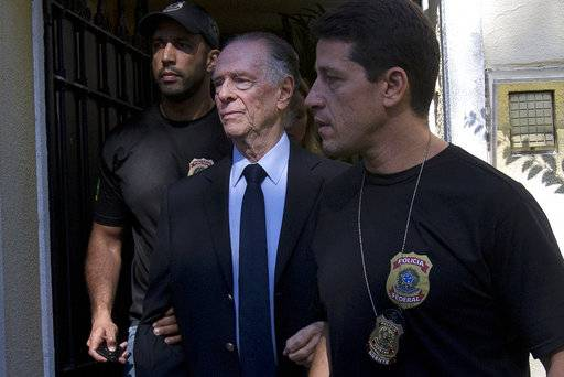 FILE - In this Oct. 5, 2017 file photo, Carlos Nuzman, president of the Brazilian Olympic Committee, is escorted by federal police officers after being taken into custody at his home, in Rio de Janeiro, Brazil. Nuzman was charged by Brazilian prosecutors Wednesday, Oct. 18, 2017, with corruption, money laundering, tax evasion, and running a criminal organization. (AP Photo/Silvia Izquierdo, File)