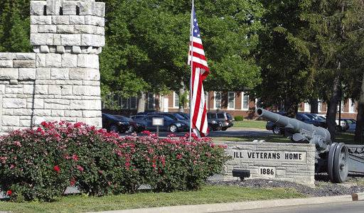 This May 18, 2012 photo shows the main entrance to the Illinois Veterans Home in Quincy, Ill. The Illinois Department of Veterans' Affairs said Wednesday, Oct. 18, 2017, that two residents at the home contracted Legionnaires' disease more than two years after an outbreak killed 12 people and sickened 54 at the facility. (Michael Kipley /Quincy Herald-Whig via AP)