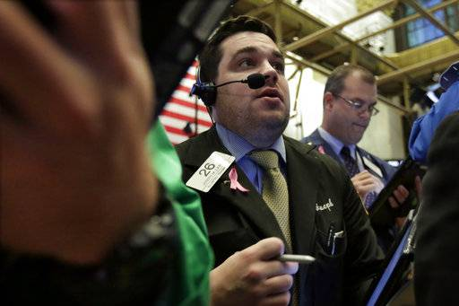 Trader Joseph Lawler, center, works on the floor of the New York Stock Exchange, Thursday, Oct. 19, 2017. Technology companies and banks are leading U.S. stocks slightly lower in early trading on Wall Street. (AP Photo/Richard Drew)