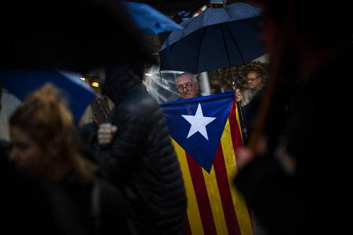 Protesters, one of them holding a pro-independence flag, gather at the gates of the Barcelona offices of the Spanish central government as they protest against the National Court's decision to imprison civil society leaders, Spain, Thursday, Oct. 19, 2017. A National Court judge ordered the preventive jailing of ANC's Jordi Sanchez and Omnium's Jordi Cuixart for allegedly orchestrating protests in mid-September that hindered a judicial probe into preparations for the Oct. 1 referendum that has been deemed unconstitutional. (AP Photo/Emilio Morenatti)