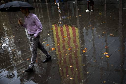 People walk past a Catalan flag reflected on the wet ground in Barcelona, Spain, Thursday, Oct. 19, 2017. Spain's government on Thursday immediately rejected a threat by Catalonia's leader to declare independence unless talks are held, calling a special Cabinet session for the weekend to activate measures to take control of the region's semi-autonomous powers.