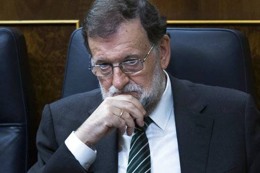 Spain's Prime Minister Mariano Rajoy listens to lawmakers during a parliamentary session at the parliament in Madrid, Wednesday, Oct. 18, 2017. About 50 Spanish and Catalan party lawmakers held up posters in the parliament demanding the release of two pro-Catalonia independence movement leaders, describing them as political prisoners.