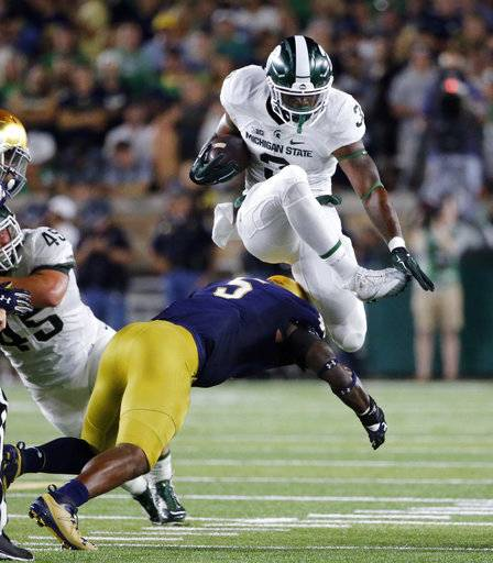 FILE - In this Sept. 17, 2016, file photo, Michigan State running back LJ Scott (3) carries the ball and hurdles Notre Dame linebacker Nyles Morgan (5) during the first half of an NCAA college football game in South Bend, Ind. No. 13 Notre Dame has adjusted well to a new defensive scheme under coordinator Mike Elko. It will face a big test on Saturday night against No. 11 Southern California, which is led by quarterback Sam Darnold. (AP Photo/Charles Rex Arbogast, File)