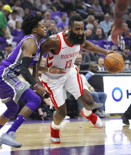 Houston Rockets guard James Harden (13) drives around Sacramento Kings defender DeAaron Fox (5) during the first half of an NBA basketball game in Sacramento, Calif., Wednesday, Oct. 18, 2017. (AP Photo/Steve Yeater)