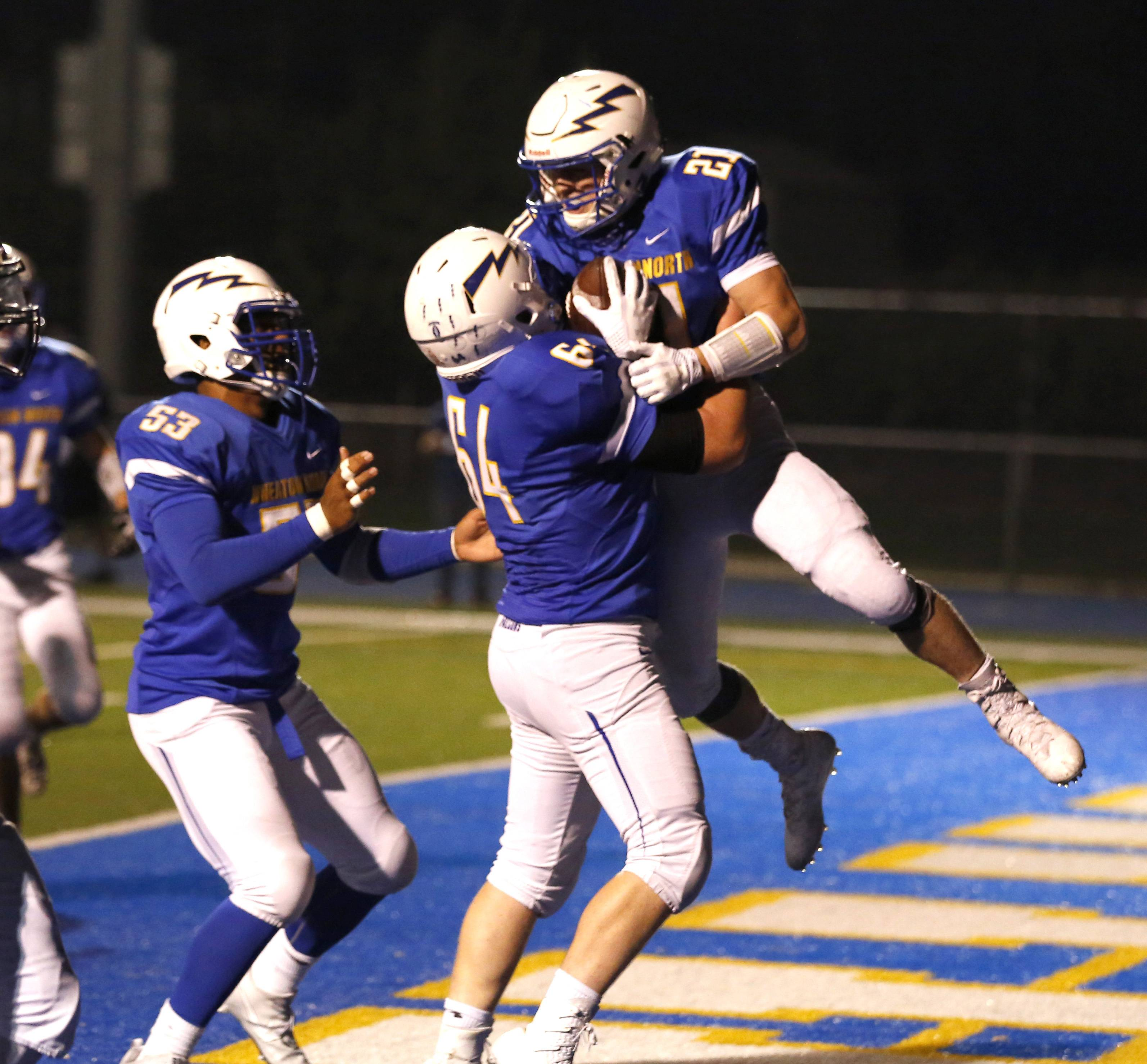Wheaton North's Sam Singleton (21) is hoisted in the air by John Willeford (64) after scoring a late second quarter touchdown against Waubonsie Valley. Richard Ficociello (53) also celebrates.
