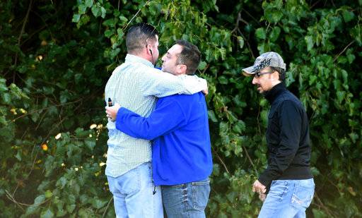 Unidentified bystanders embrace as police and Emergency Medical Services respond to a shooting at a business park in the Edgewood area of Harford County, Md., Wednesday, Oct. 8, 2017. (Matt Button/The Baltimore Sun via AP)