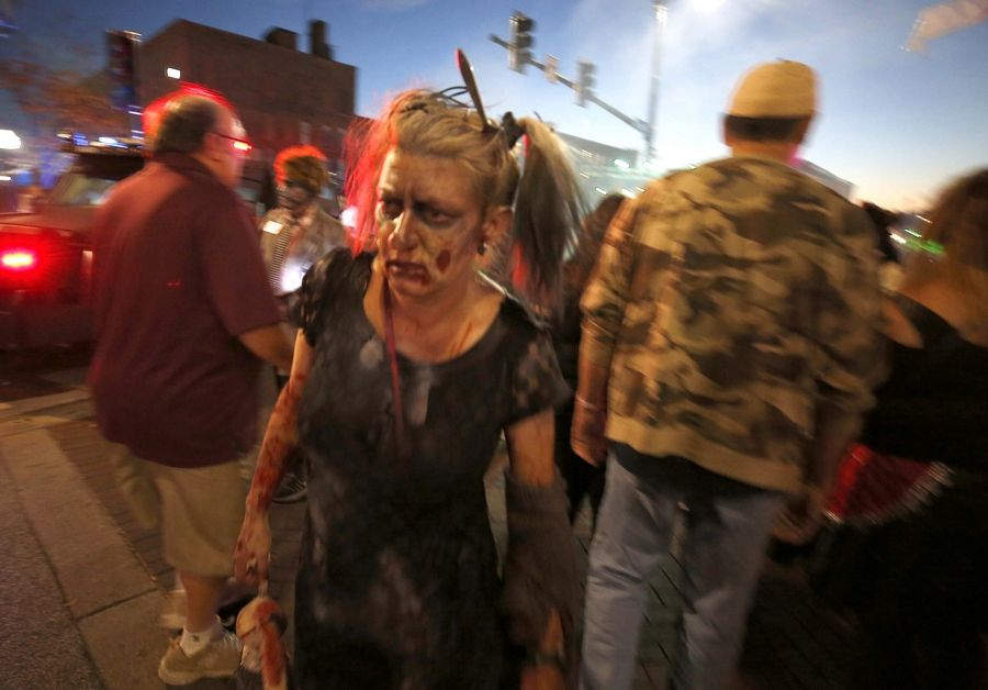 A zombie stumbles through the crowd Saturday during Nightmare on Chicago Street in Elgin.