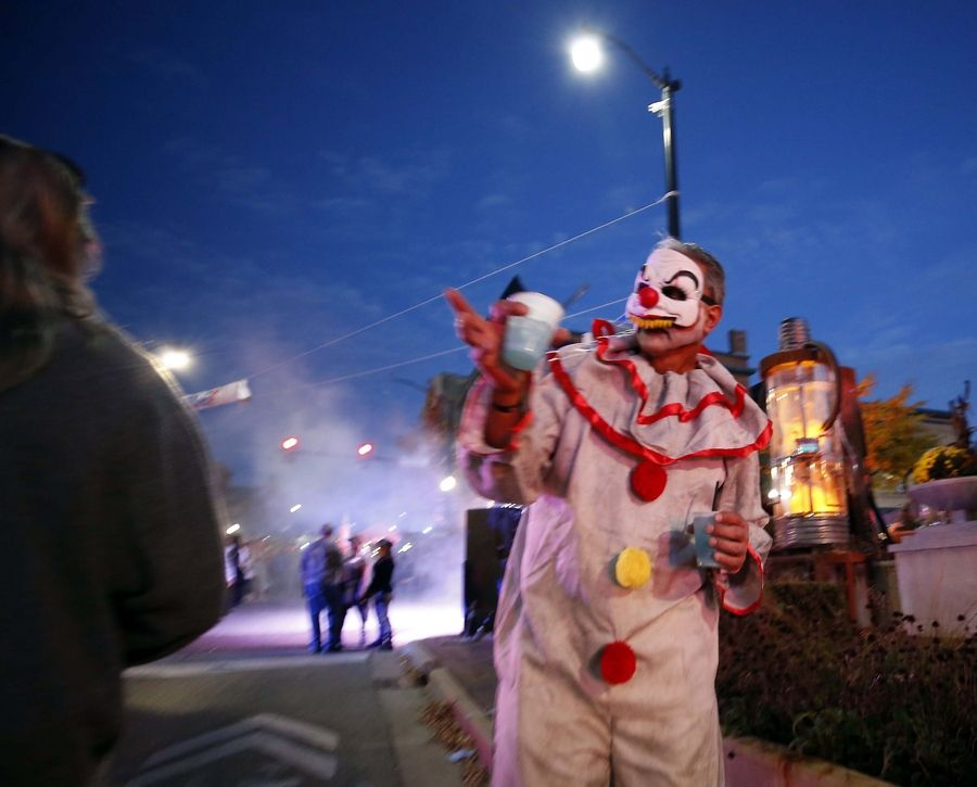 A scary clown walks down Chicago Street during Nightmare on Chicago Street on Saturday in Elgin.