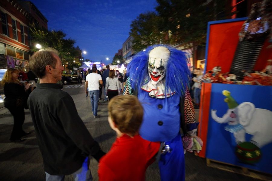 A scary clown walks down Chicago Street on Saturday during Nightmare on Chicago Street in Elgin.