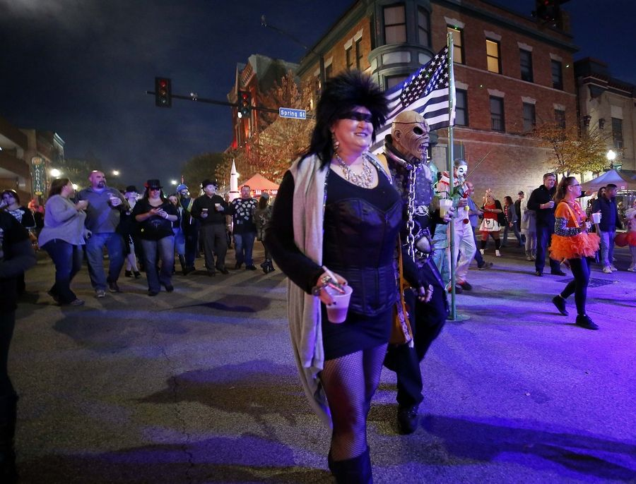 Colleen Pridemore and Mark Minter, both of Elgin, stroll down Chicago Street on Saturday during Nightmare on Chicago Street in Elgin.