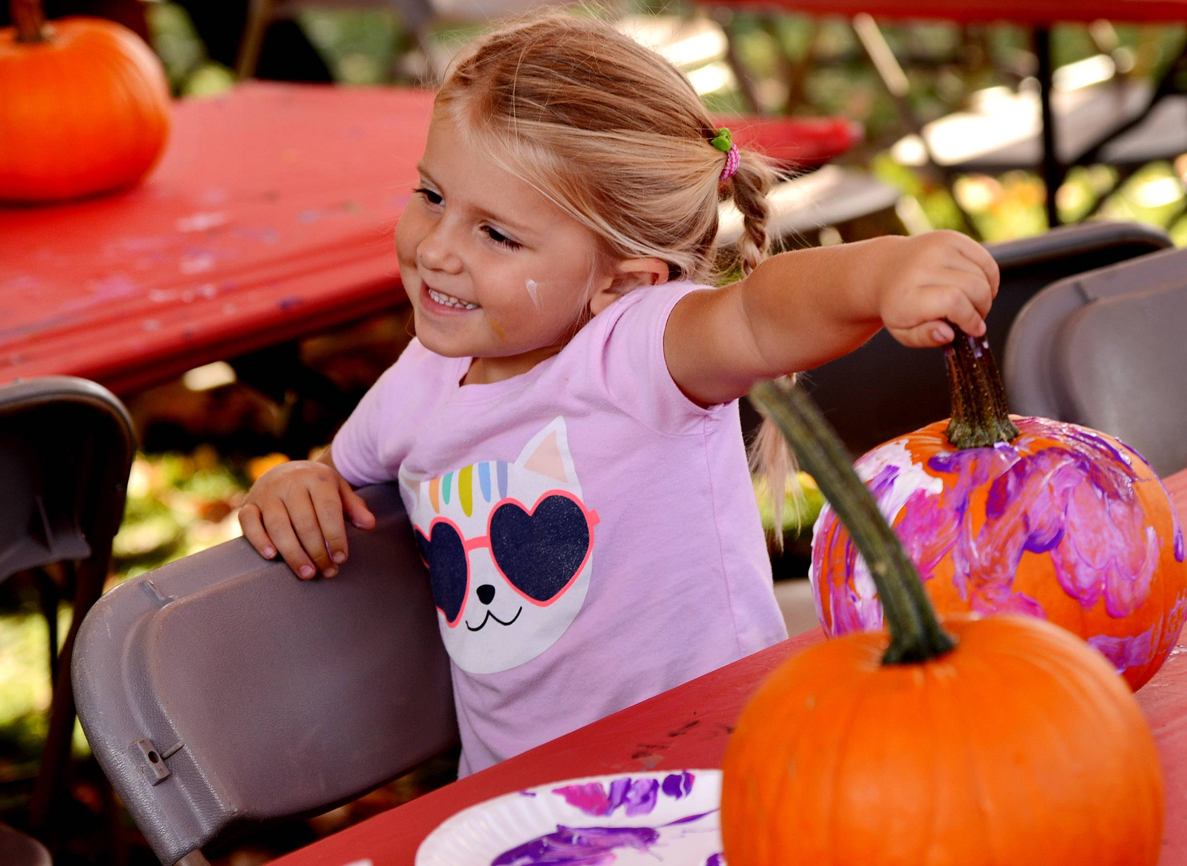 Eliana Collins, 4, of Barrington shows off the pumpkin she just painted to her dad Mike Collins, as fall enthusiasts flocked Saturday to Barrington's 17th annual Scarecrow Festival.