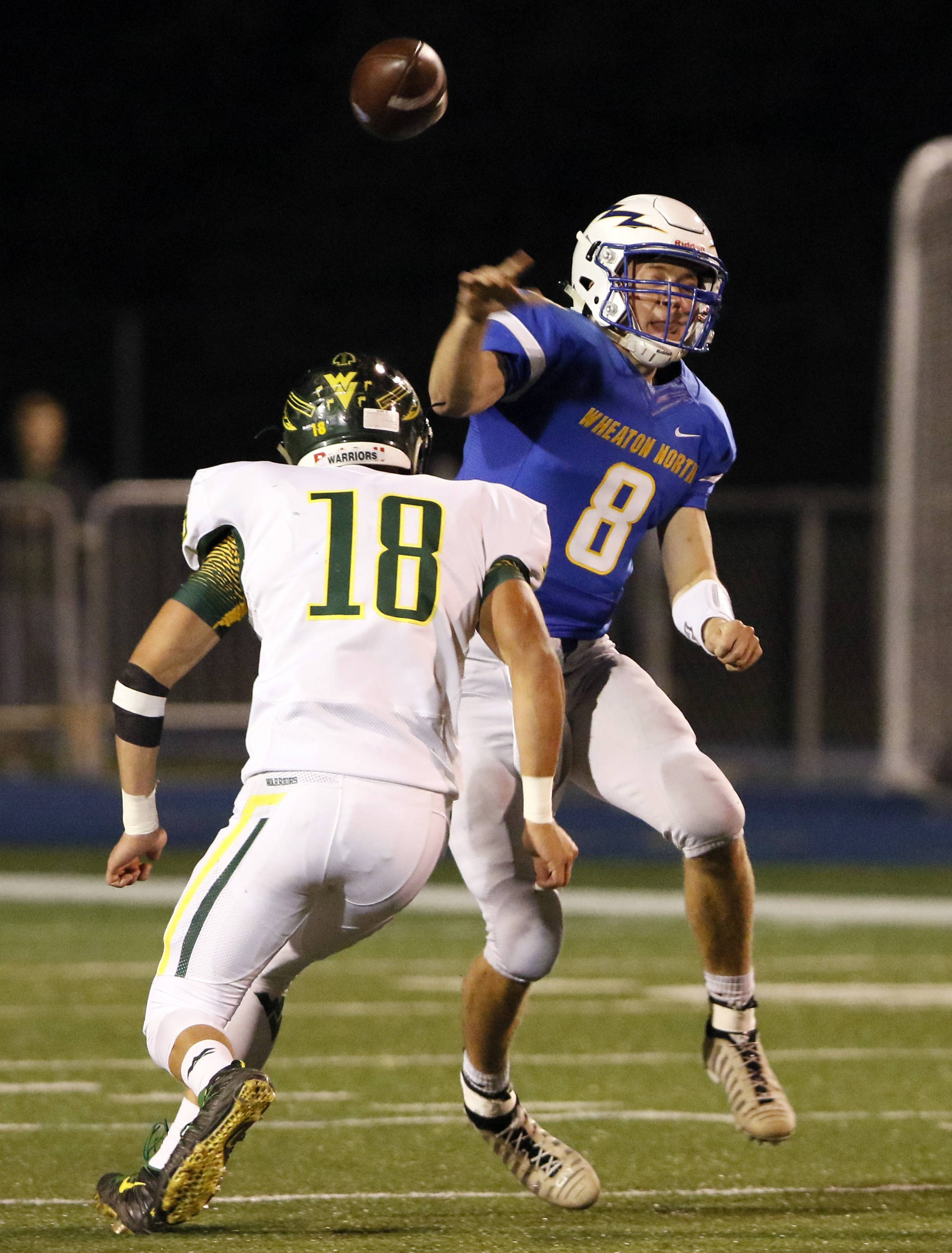 Wheaton North quarterback Rhett Netzer (8) fires a pass around Waubonsie Valley's Eric France (18) during football action in Wheaton.