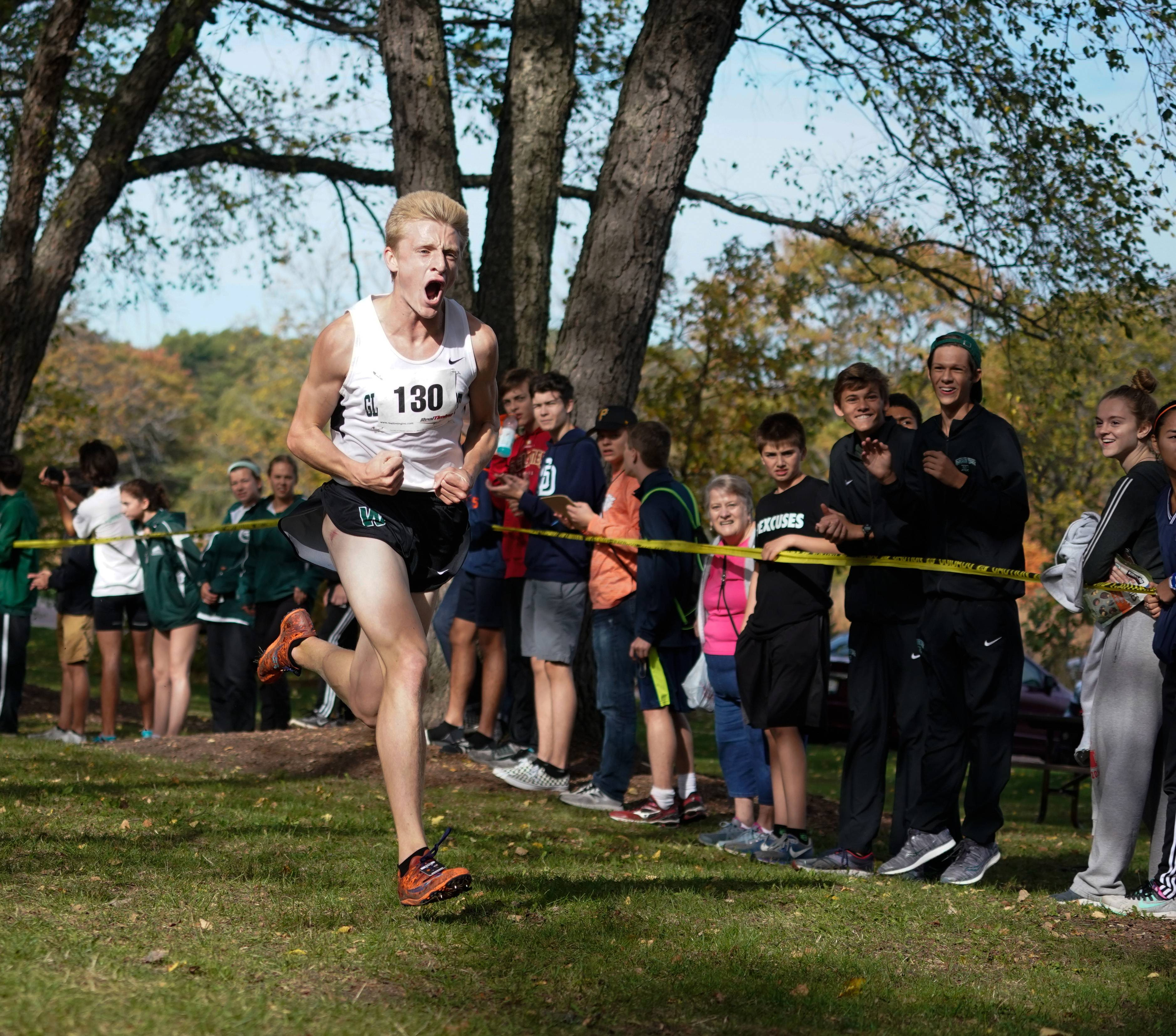 Glenbard West's Rory Cavan celebrates as he approaches the finish line first in the Boys Class 3A Wheaton North cross country regional at St. James Farm Forest Preserve in Warrenville, IL on Saturday, October 21, 2017