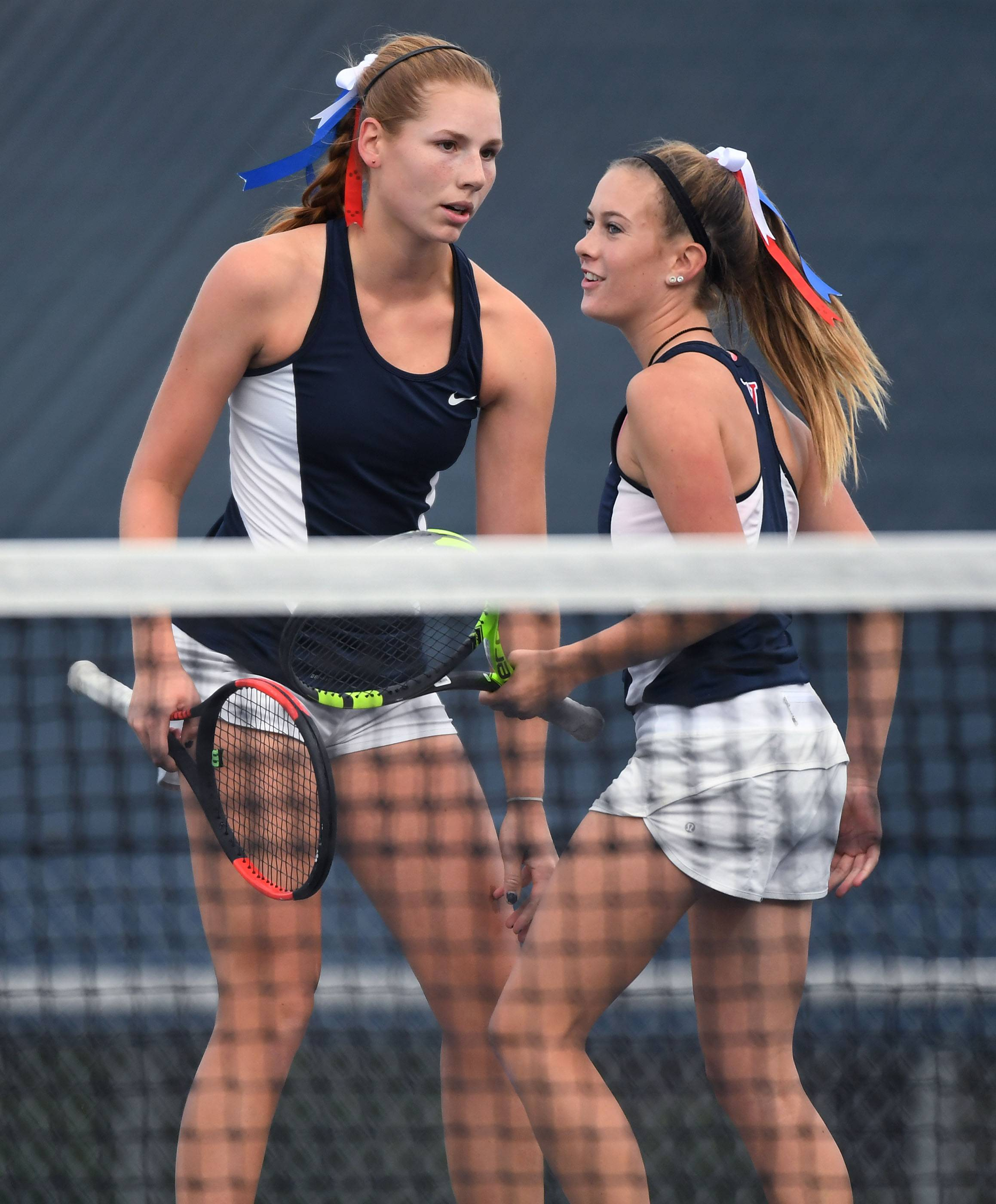 West Aurora's Maria Goheen, left, and Liz Stefancic strategize against Hinsdale Central's Sarah Dadawi and Kathryn Treiber in the Class 2A doubles semifinal match Saturday at the IHSA state finals at Buffalo Grove High School. Goheen and Stefancic went on to win the state title.