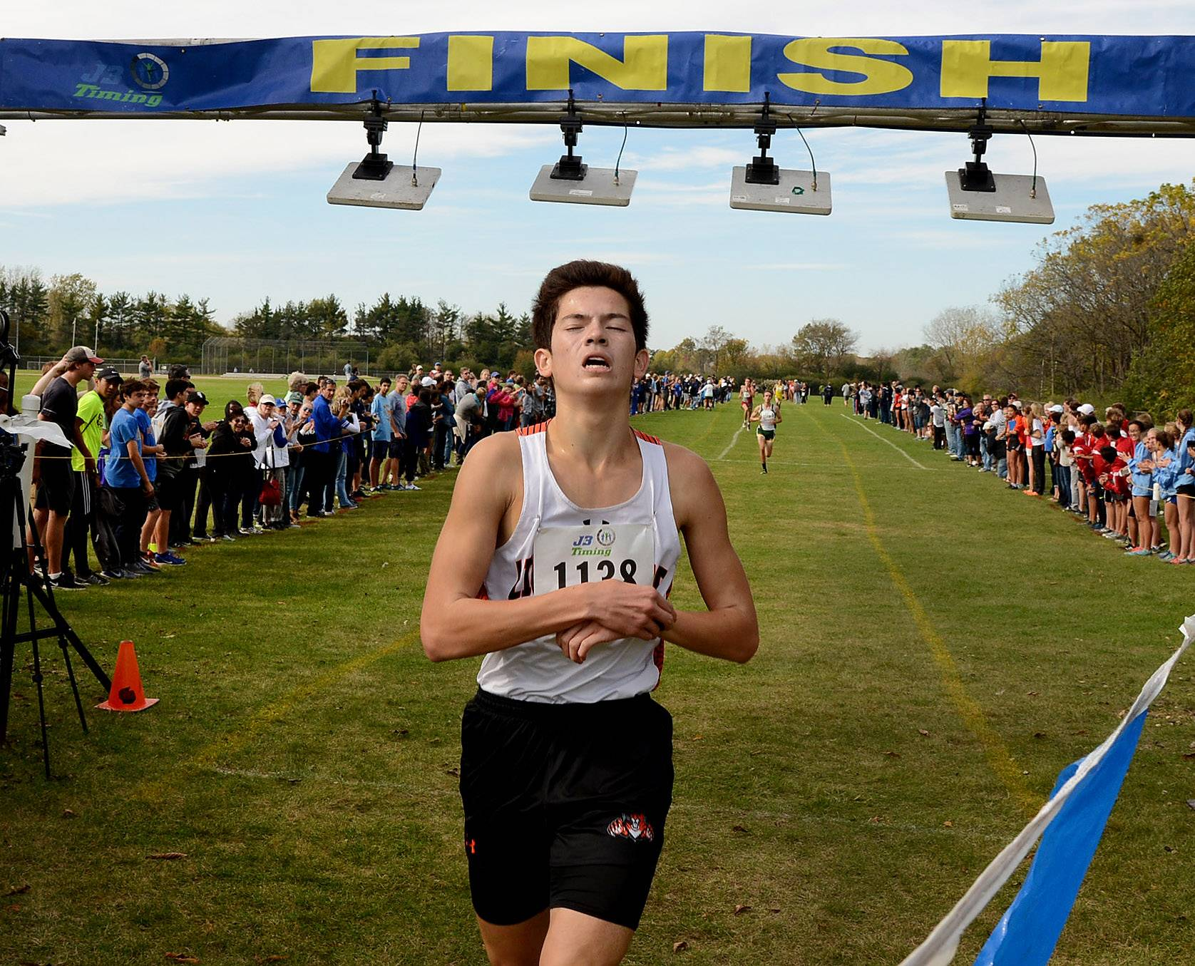 Alex Tam of Libertyville sets his watch while crossing the finish line in first in 14:52.5 during the Class 3A Lake Forest cross country regional.