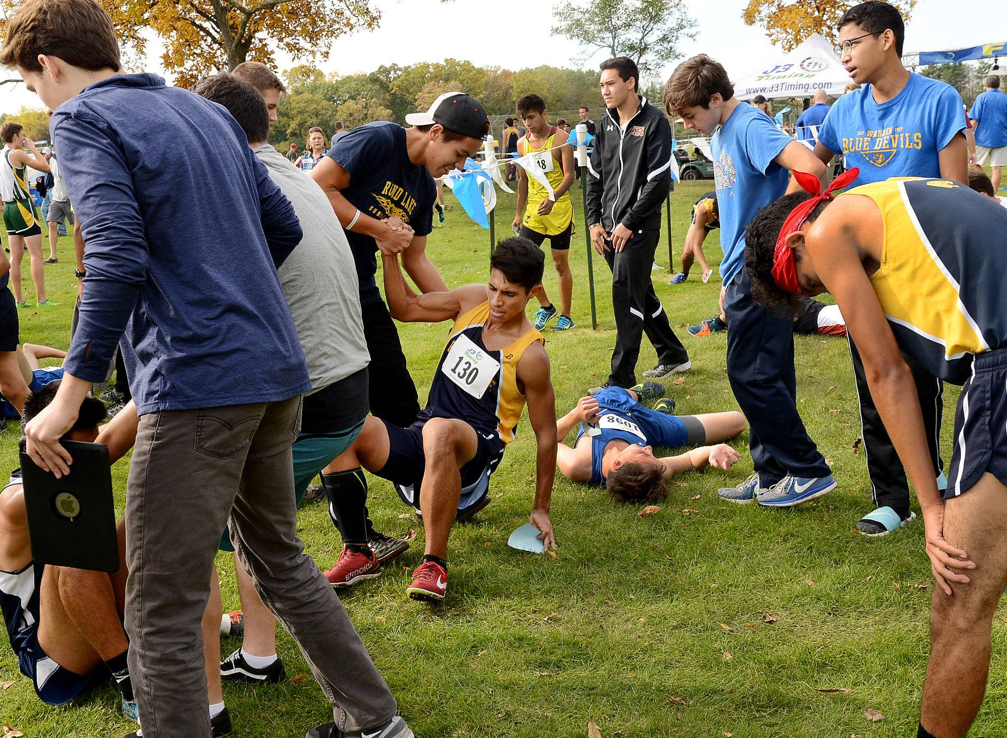 Round Lake runner Sam Ruiz, left, is helped up after finishing 46th during the Class 3A Lake Forest cross country regional.