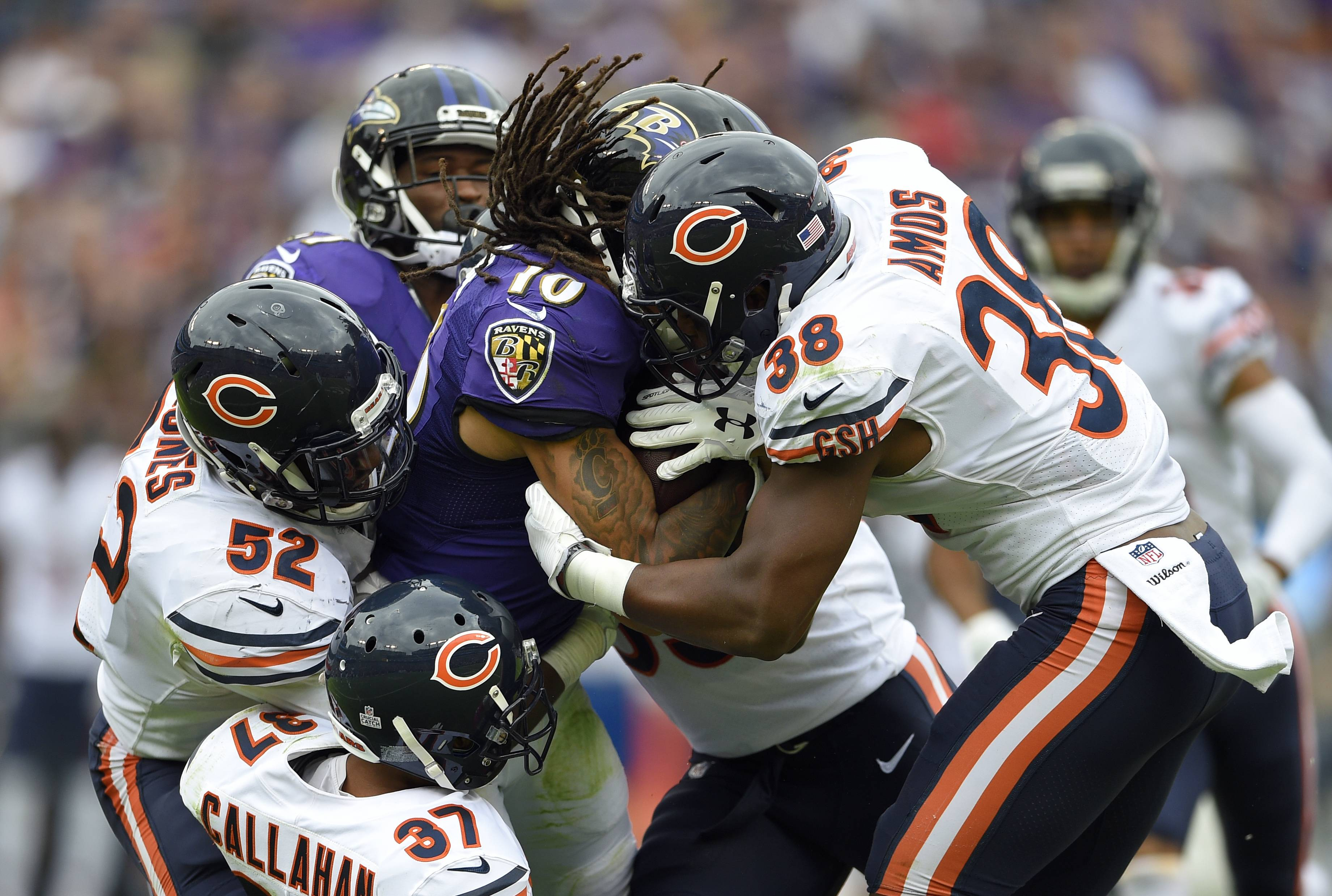 Baltimore Ravens wide receiver Chris Moore (10) is tackled by Chicago Bears defenders as he rushes the ball in the second half of an NFL football game, Sunday, Oct. 15, 2017, in Baltimore.