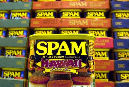 "FILE - This March 3, 2004 file photo shows a collector's limited edition ""Hawaii"" can of Spam, with a hula doll on both sides of the can and a picture of three pieces of spam musubi in Kailua, Hawaii. Cans of Spam have become a common item that's being stolen from Honolulu stores and then sold on the streets for quick cash, according to authorities. The state's love affair with Spam began during World War II, when rationing created just the right conditions for the rise of a meat that needs no refrigeration and has a remarkably long shelf life (indefinitely, the company says). (AP Photo/Lucy Pemoni, File)"