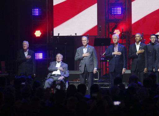Former Presidents from right, Barack Obama, Bill Clinton, George W. Bush, George H.W. Bush and Jimmy Carter place their hands on their chest for the national anthem on stage at the opening of a hurricanes relief concert in College Station, Texas, Saturday, Oct. 21, 2017. All five living former U.S. presidents joined to support a Texas concert raising money for relief efforts from Hurricane Harvey, Irma and Maria's devastation in Texas, Florida, Puerto Rico and the U.S. Virgin Islands. (AP Photo/LM Otero)