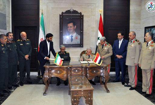 In this photo released by the Syrian official news agency SANA, the Chief of Staff of Iran's armed forces, Maj. Gen. Mohammad Bagheri, center left, attends as his Syrian counterpart Gen. Ali Ayoub, center right, signs a joint memorandum of understanding for developing cooperation and coordination between the two countries' armies in Damascus, Syria, Saturday, Oct. 21, 2017. State news agency SANA said the memo provides for exchanging military expertise and intelligence and technology information in a way that can boost the two countries' capability for fight terrorism. (SANA via AP)