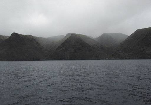 In this Oct. 15, 2017, photo, the forbidding volcanic cliffs of St. Helena island are covered in fog. Tourists who take a cruise out of Jamestown, the island's capital, can sometimes see pods of dolphins, humpback whales and seabirds nesting in the walls of rock along the shoreline. (AP photo/Christopher Torchia)