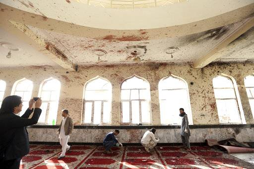 Afghans inspect inside a damaged mosque in Kabul, Afghanistan, Saturday, Oct. 21, 2017, a day after a suicide attack. Suicide bombers struck two mosques in Afghanistan during Friday prayers, the Shiite mosque in Kabul and a Sunni mosque in western Ghor province at the end of a particularly deadly week for the troubled nation. (AP Photo/Rahmat Gul)