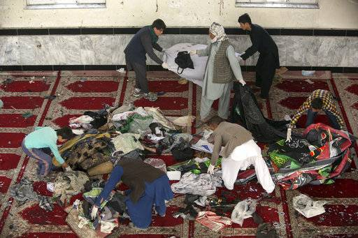 Afghan men collect remains of belongings inside a damaged mosque in Kabul, Afghanistan, Saturday, Oct. 21, 2017, a day after a suicide attack. Suicide bombers struck two mosques in Afghanistan during Friday prayers, the Shiite mosque in Kabul and a Sunni mosque in western Ghor province at the end of a particularly deadly week for the troubled nation. (AP Photo/Rahmat Gul)