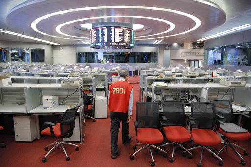 In this Oct. 19, 2017, photo, Yip Wing-keung, a trading manager at local brokerage Christfund Securities, wearing his red trading jacket, walks at the Hong Kong Stock Exchange. Hong Kong's last remaining stock market floor traders are taking their final orders as the exchange prepares to shut its trading hall, joining other world exchanges in going fully automated. (AP Photo/Kin Cheung)