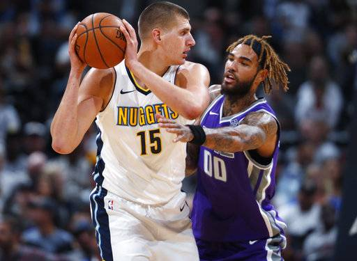 Denver Nuggets center Nikola Jokic, left, of Serbia, looks to pass the ball as Sacramento Kings center Willie Cauley-Stein defends in the first half of an NBA basketball game Saturday, Oct. 21, 2017, in Denver. (AP Photo/David Zalubowski)
