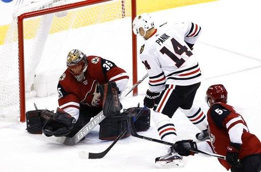 Chicago Blackhawks' Richard Panik (14) scores a goal against Arizona Coyotes' Louis Domingue (35) as Coyotes' Jason Demers (55) looks on during the first period of an NHL hockey game Saturday, Oct. 21, 2017, in Glendale, Ariz. (AP Photo/Ross D. Franklin)