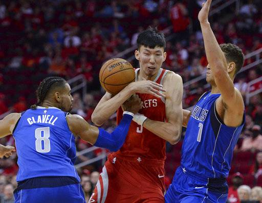 Houston Rockets center Zhou Qi (9) loses the ball as he is defended by Dallas Mavericks Gian Clavell (8) and Dennis Smith Jr. (1) in the second half of an NBA basketball game Saturday, Oct. 21, 2017, in Houston. (AP Photo/George Bridges)