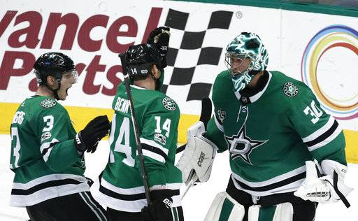 Dallas Stars goalie Ben Bishop, wing Jamie Benn (14) and defenseman John Klingberg (3) celebrate after defeating the Carolina Hurricanes in an NHL hockey game, Saturday, Oct. 21, 2017, in Dallas. (AP Photo/Mike Stone)