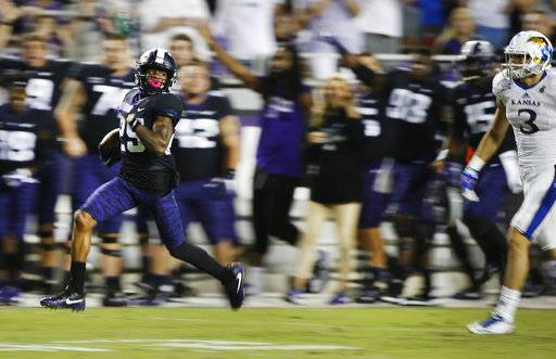 TCU's KaVontae Turpin returns a punt 90 yards for a touchdown as Kansas' Chase Harrell (3) during the second half of an NCAA college football game Saturday, Oct. 21, 2017, in Fort Worth, Texas. TCU won 43-0. (AP Photo/Ron Jenkins)