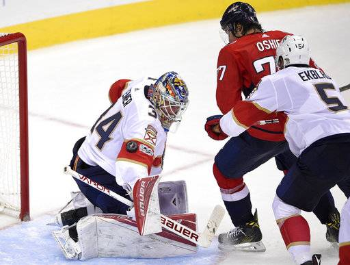 Florida Panthers goalie James Reimer (34) watches the puck in front of Washington Capitals right wing T.J. Oshie (77) during the third period of an NHL hockey game, Saturday, Oct. 21, 2017, in Washington. At right is Panthers defenseman Aaron Ekblad (5). The Panthers won 4-1. (AP Photo/Nick Wass)