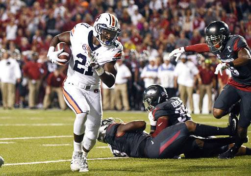 Auburn running back Kerryon Johnson, left, runs around the Arkansas defense to score a touchdown in the first half of an NCAA college football game in Fayetteville, Ark., Saturday, Oct. 21, 2017. (AP Photo/Michael Woods)