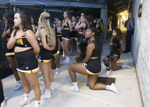 Four of the five Kennesaw State cheerleaders who took a knee three weeks ago during the Kennesaw State football game, take a knee once again out of sight of the fans under the visitors' bleachers, during the national anthem before an NCAA college football game between Kennesaw State and Gardner-Webb, Saturday, Oct. 21, 2017, in Kennesaw, Ga. The cheerleaders are kneeling in protest police brutality. (Kelly J. Huff/The Marietta Daily Journal via AP)