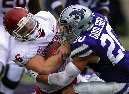 Oklahoma quarterback Baker Mayfield (6) is tackled by Kansas State defensive back Denzel Goolsby (20) during the first half of an NCAA college football game in Manhattan, Kan., Saturday, Oct. 21, 2017. (AP Photo/Orlin Wagner)