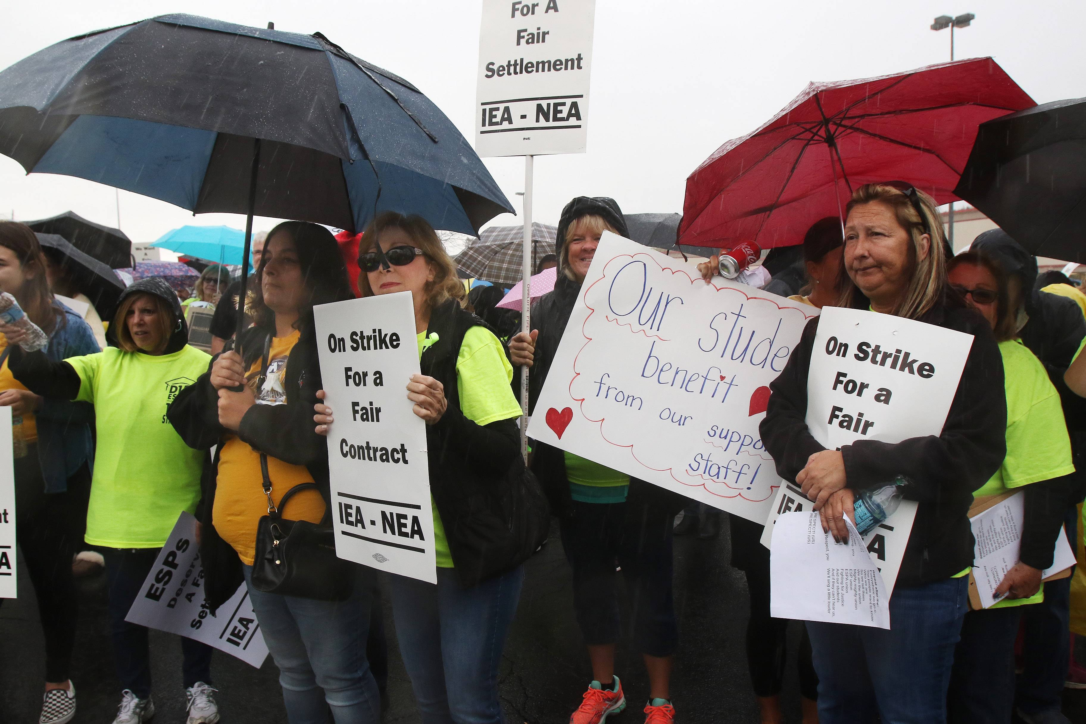 Striking Palatine Township Elementary District 15 workers and their supporters stand in the rain Sunday morning during a rally by the Educational Support Personnel Association. After the rally, they marched to District 15 headquarters, where negotiations resumed.