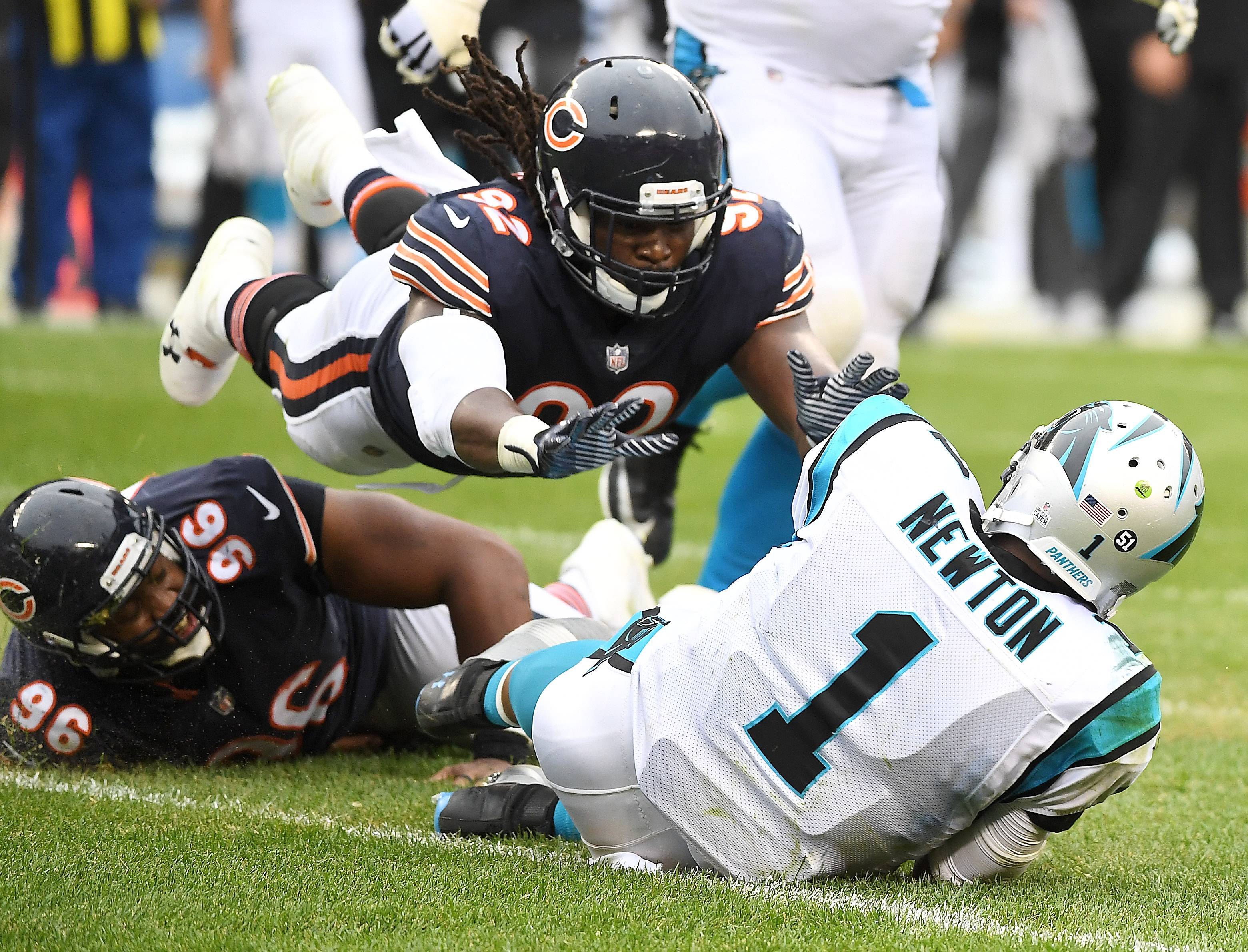 Chicago Bears outside linebacker Pernell McPhee flies over teammate Akiem Hicks to land on Carolina Panthers quarterback Cam Newton during Sunday's game at Soldier Field in Chicago.