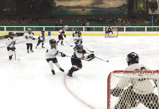 The Santa Rosa Flyers hockey players, ages 7 and 8, take to the ice for the first time Sunday, Oct. 22, 2017 in Santa Rosa, Calif., since wildfires tore through California's wine country starting Oct. 8. The annual hockey tournament for 7- and 8-year-olds was held as scheduled Sunday at Snoopy's Home Ice, the rink financed by Peanuts creator Charles Schultz, a Santa Rosa native and hockey fan. (AP Photo/Paul Elias)