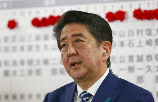 Japanese Prime Minister Shinzo Abe, leader of the Liberal Democratic Party, answers a question from reporter during a TV interview on the ballot counting of the parliamentary lower house election at the party headquarters in Tokyo, Sunday, Oct. 22, 2017. Japanese media projected shortly after polls closed that Prime Minister Shinzo Abe's ruling coalition would win a clear majority in national elections.(AP Photo/Shizuo Kambayashi)