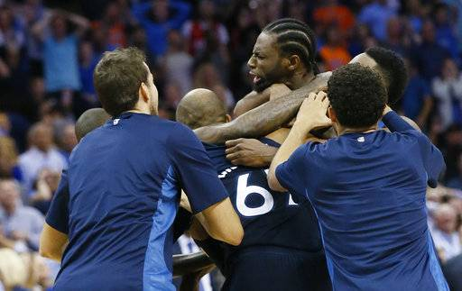 Minnesota Timberwolves guard Andrew Wiggins, center, is mobbed by his teammates after hitting the game winning shot at the buzzer in the fourth quarter of an NBA basketball game against the Oklahoma City Thunder in Oklahoma City, Sunday, Oct. 22, 2017. Minnesota won 115-113. (AP Photo/Sue Ogrocki)