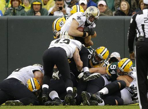 New Orleans Saints quarterback Drew Brees (9) dives over for a touchdown during the second half of an NFL football game against the Green Bay Packers, Sunday, Oct. 22, 2017, in Green Bay, Wis. (AP Photo/Jeffrey Phelps)