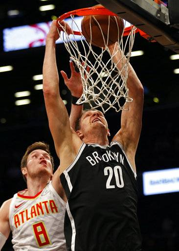 Brooklyn Nets' Timofey Mozgov slam-dunks the ball in front of Atlanta Hawks' Luke Babbitt (8) during the second quarter of an NBA basketball game Sunday, Oct. 22, 2017, in New York. (AP Photo/Adam Hunger)