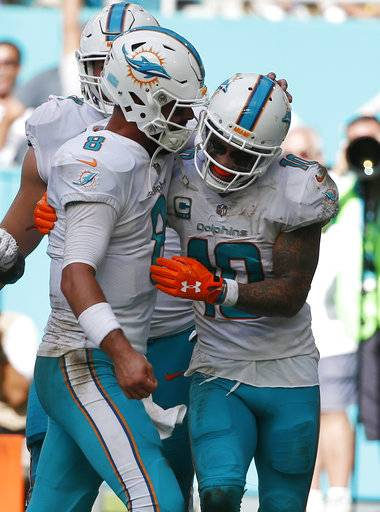 Miami Dolphins quarterback Matt Moore (8) celebrates a touchdown with Miami Dolphins wide receiver Kenny Stills (10), during the second half of an NFL football game against the New York Jets, Sunday, Oct. 22, 2017, in Miami Gardens, Fla. (AP Photo/Wilfredo Lee)