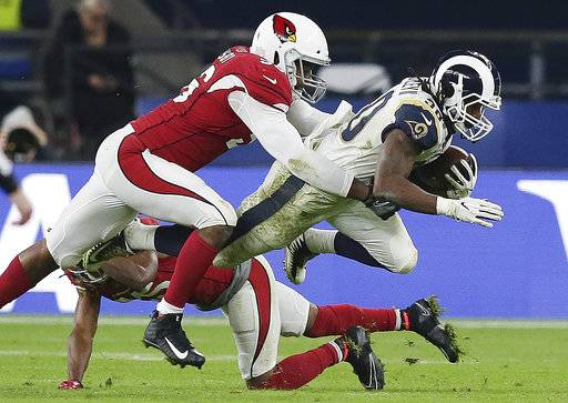 Los Angeles Rams running back Todd Gurley (30) is tackled by Arizona Cardinals inside linebacker Karlos Dansby (56) during the second half of an NFL football game against Arizona Cardinals at Twickenham Stadium in London, Sunday Oct. 22, 2017. (AP Photo/Tim Ireland)